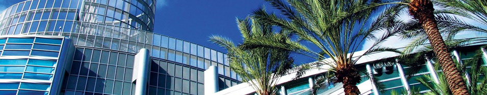 Photo of a beautiful sunny day at a convention center with palm trees out front.